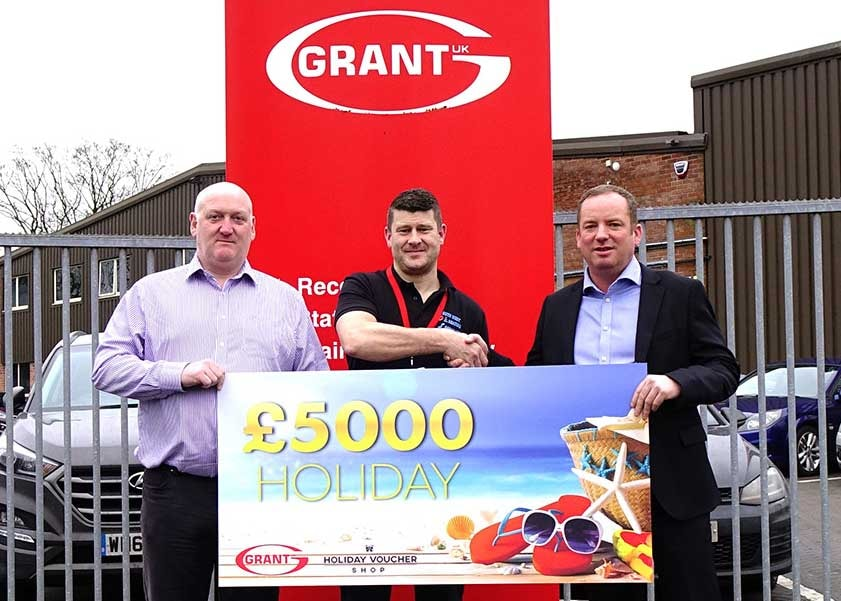 Ryan Hosking of SOS Heating is presented with his £5,000 holiday vouchers won through the Big G1 Giveaway by Andy Smith, National Sales Manager at Grant UK, right and Stewart Ratcliff, Area Sales Manager for the South West at Grant UK, left