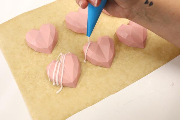 Piping royal icing onto geo cake hearts