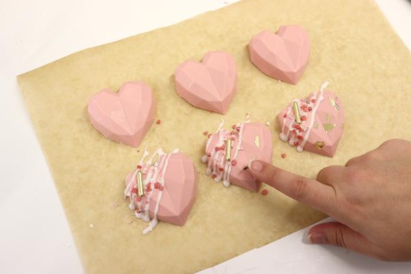 Adding sprinkles to geo cake hearts