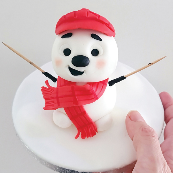 Fondant snowman with arms and legs attached.