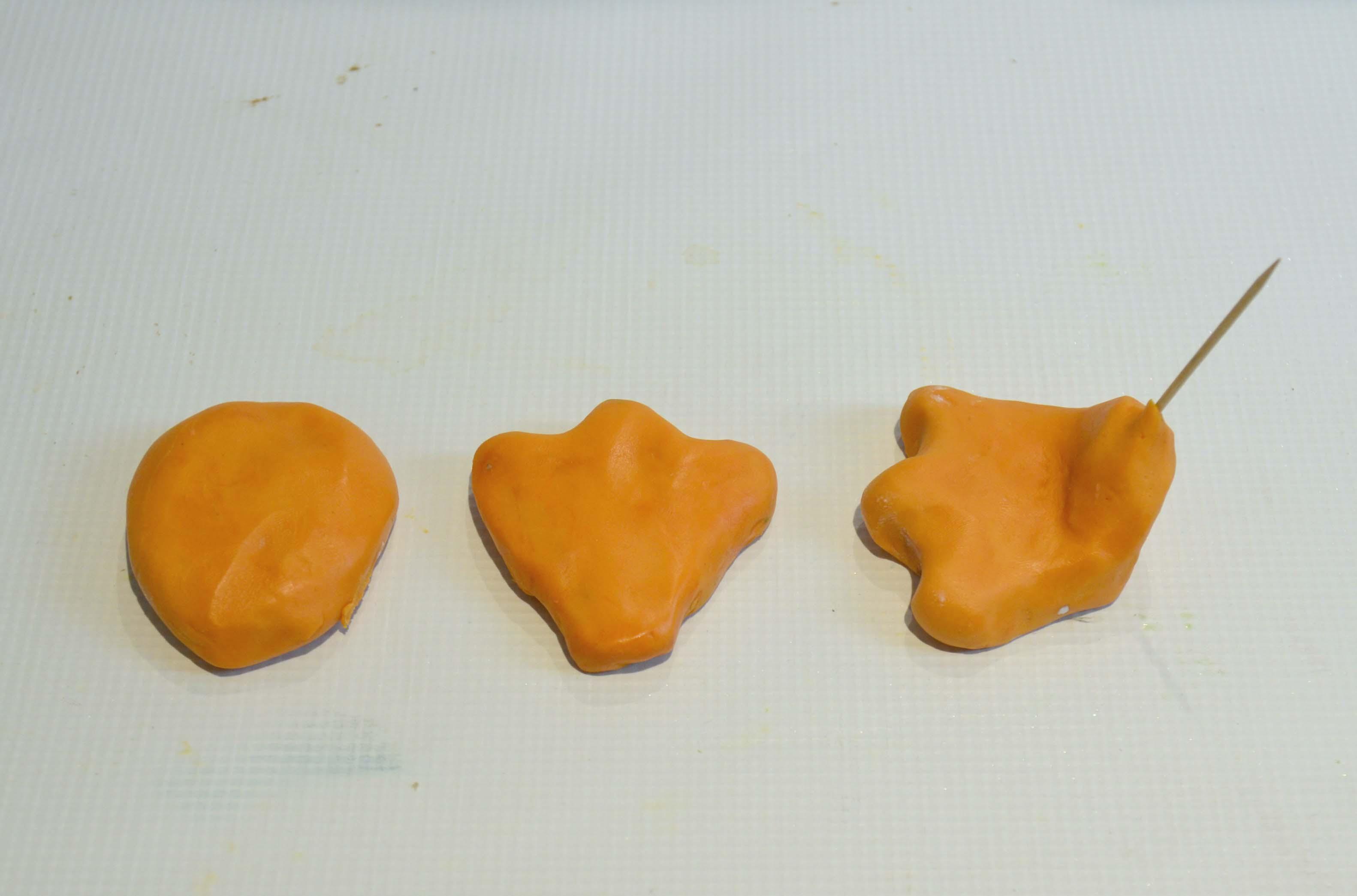 Creating two feet using orange sugarpaste