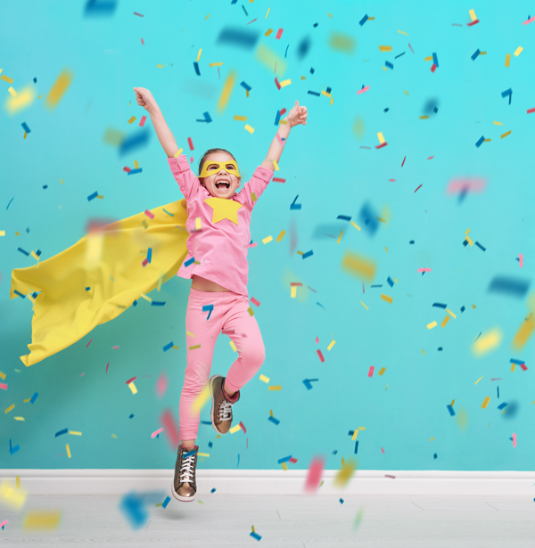 child in superhero outfit celebrating