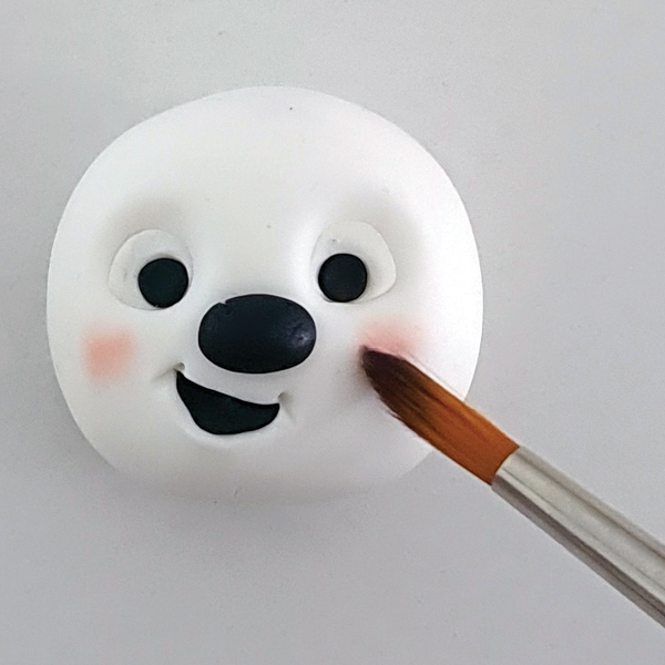 Fondant snowman with rosy cheeks.