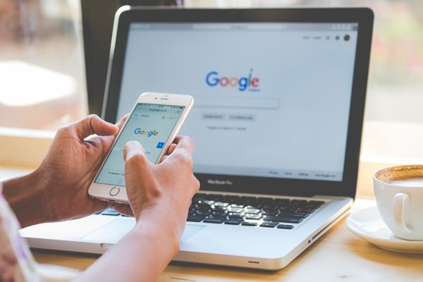 Google search engine on phone and laptop