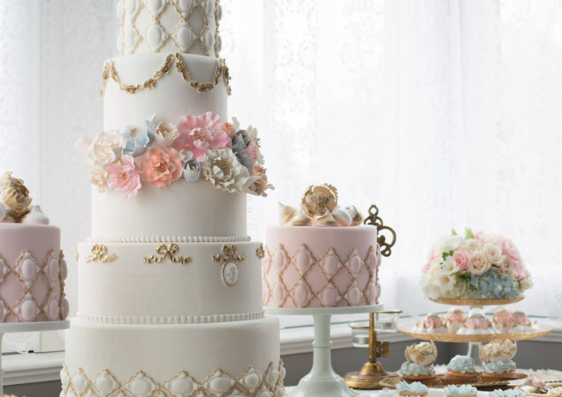 White and pink tiered cakes with pastel-coloured flowers
