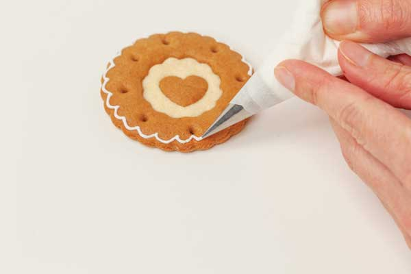 Gingerbread cookies with white royal icing being piped on the edge