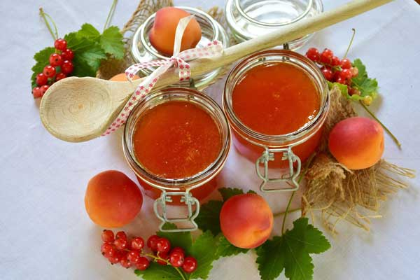 Apricot jam jars with wooden spoon