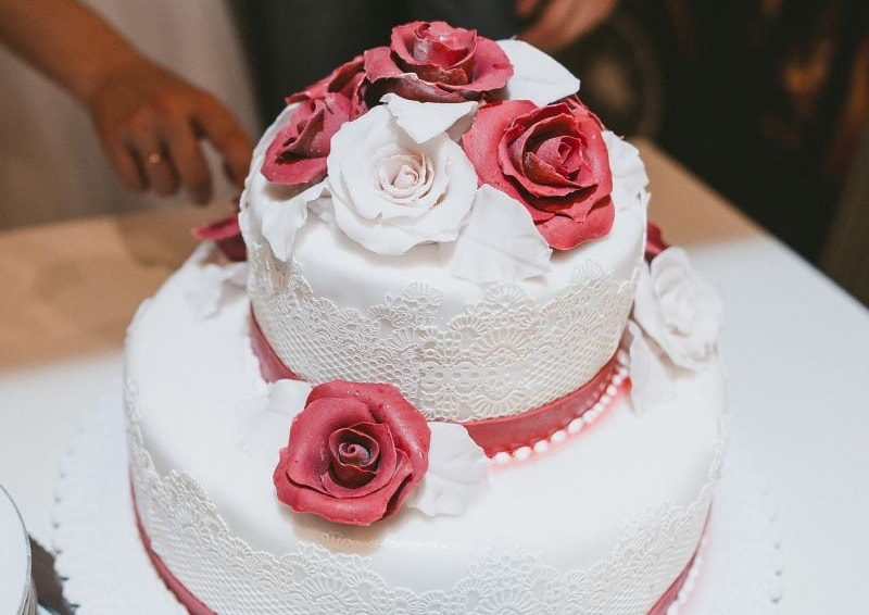 Two-tiered wedding cake covered in sugarpaste with flowers