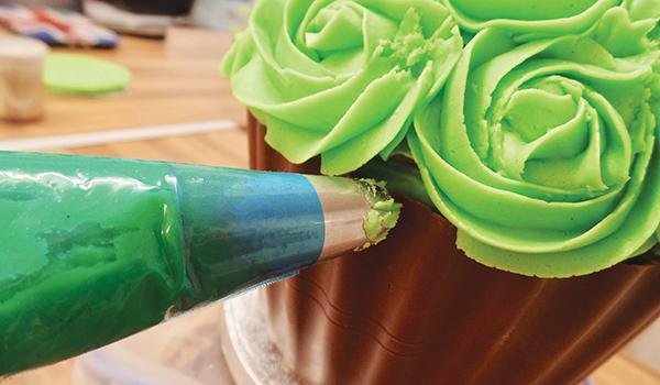Piping green buttercream swirls