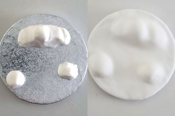 Cake board with white sugarpaste lumps to create a snowy landscape