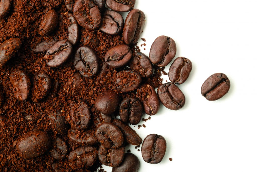Ground coffee and beans scattered across a white background.