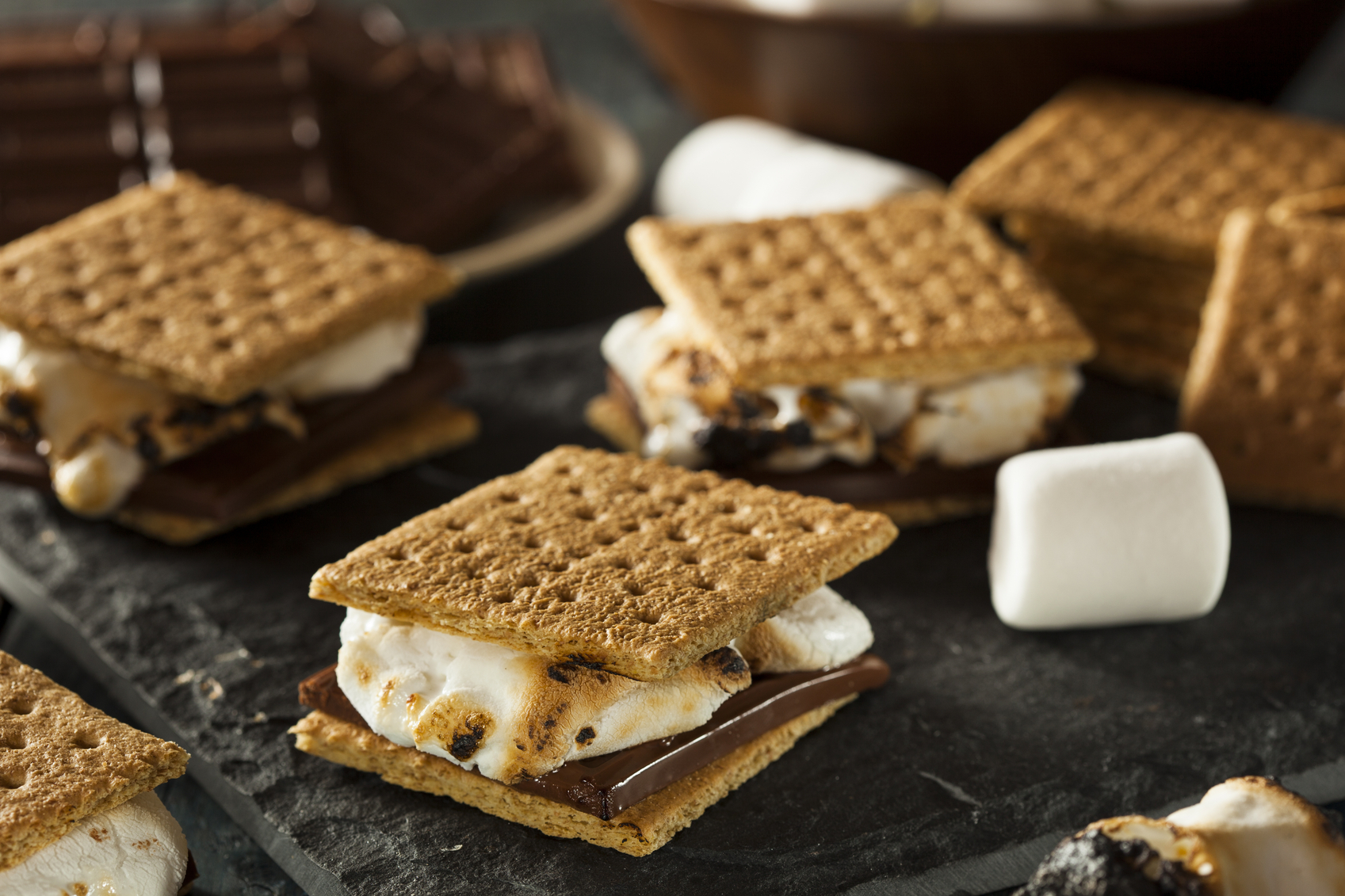 A counter top hosts seven s'mores featuring graham crackers, white marshmallows and thick chocolate slices.  The s'more dessert sandwiches are thick.  Each graham cracker, marshmallow filling and dark chocolate filling rests at a slightly different angle causing every dessert sandwich to look unique.