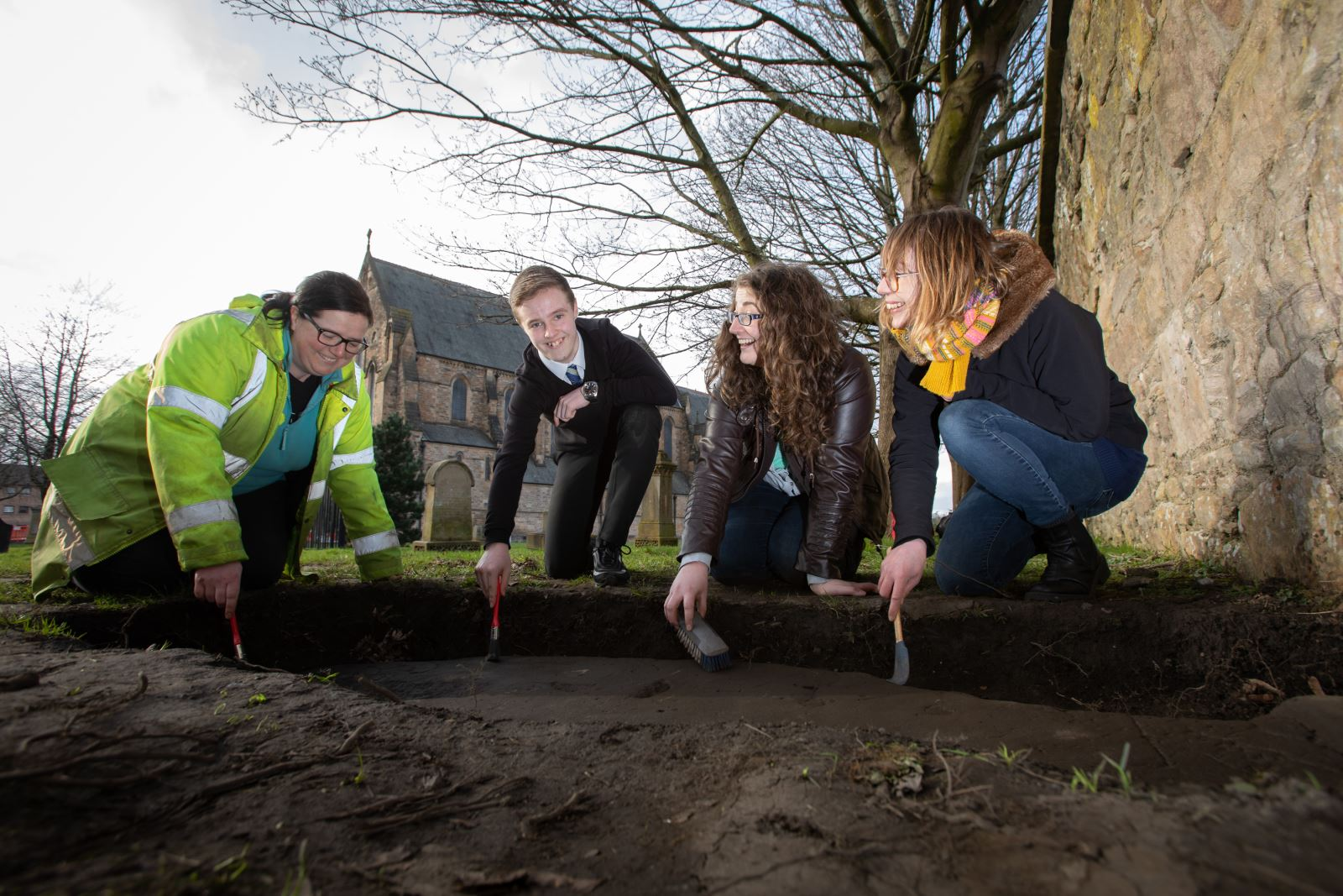 Nicola Reid, Field Archaeolgist, Northlight Heritage; Mark McGettigan, aged 14; Megan Kasten, Project Office & Volunteer, Northlight Heritage and Ingrid Shearer, Community Engagement Officer for Stones & Bones excavation, Northlight Heritage examining one of the three Govan Stones rediscovered at Govan Old Parish Church
