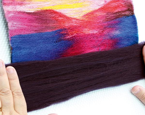 Covering remaining felt with Aubergine Merino wool top fibres