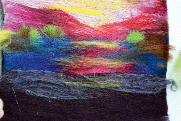 Placing coloured wool top fibres in centre and stabbing them in