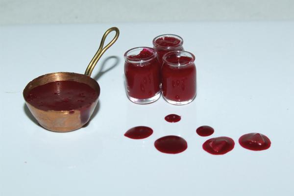 Dripping jam into miniature jars and miniature jam pan