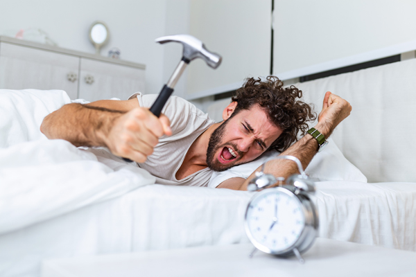man about to hit alarm clock with hammer