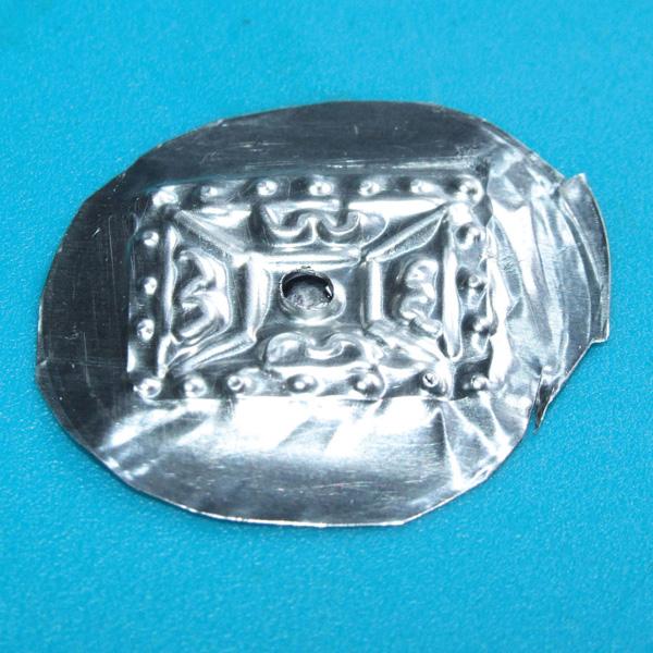 Circular metal flattened with embossed design