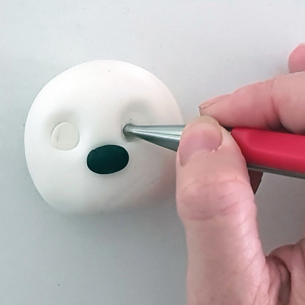 Fondant snowman with holes being made in the eyes.