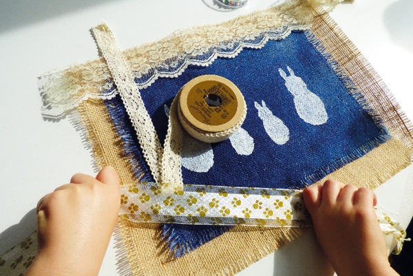 Arranging lace and ribbons on hessian fabric