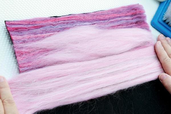 Layer of Alpaca Pink wool top fibres on the felt sky