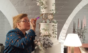 Christine-Jensen-setting-up-a-tiered-cake-in-venue