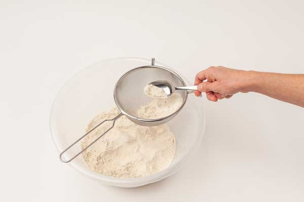 Flour mixture being sieved into a bowl