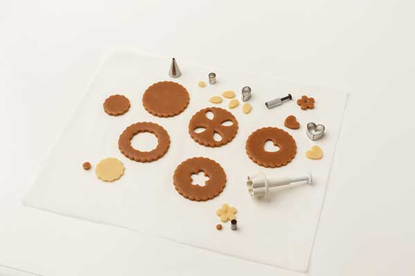 Gingerbread dough cut into cookie shapes
