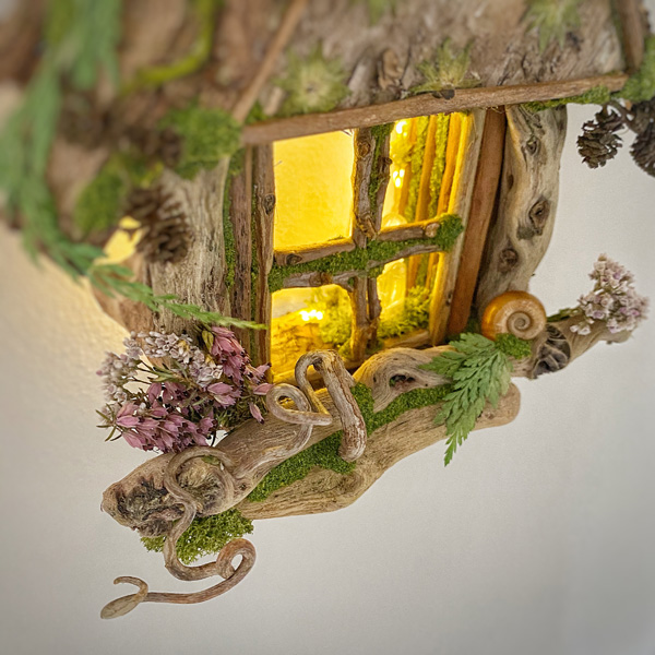 Wall hung driftwood and bark dormer window, lit by twinkling fairy lights, by Gemma Harris