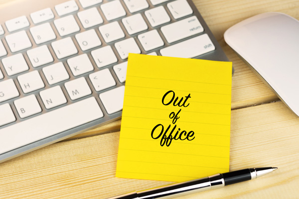 out of office Post-it on a keyboard