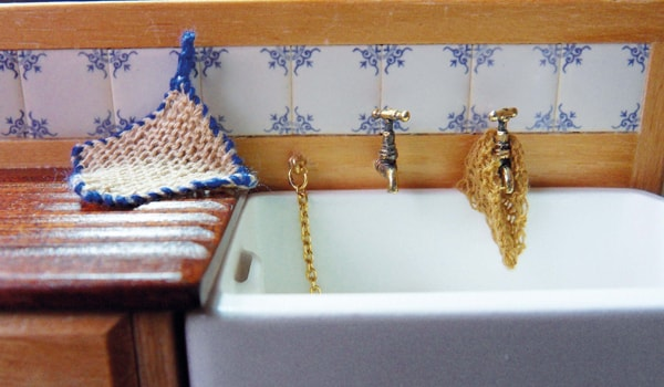 miniature knitted dish cloth and pot holder on sink