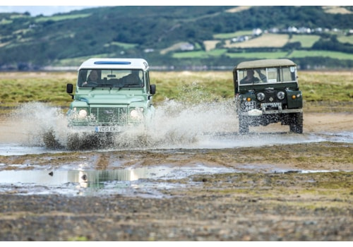 2015 Heritage Edition Defender 110 and 1952 Series I on beach, Red Wharf Bay, Anglesey