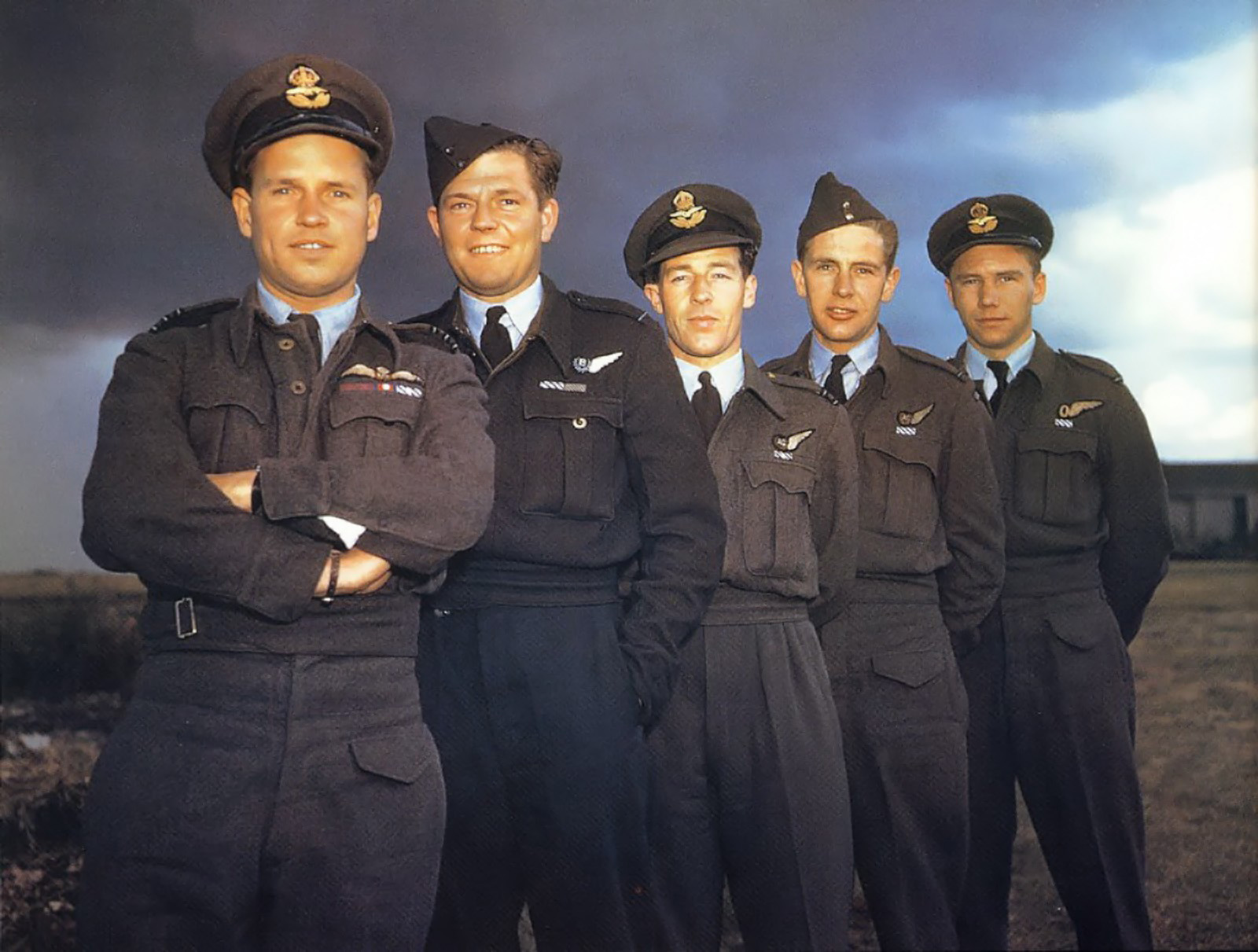 Wing Commander Guy Gibson (front) and the crew of AJ-G. The purple medal ribbon, below the aircrew brevet (officially known as an aircrew badge) on Gibson's tunic, is that of the Victoria Cross (VC)