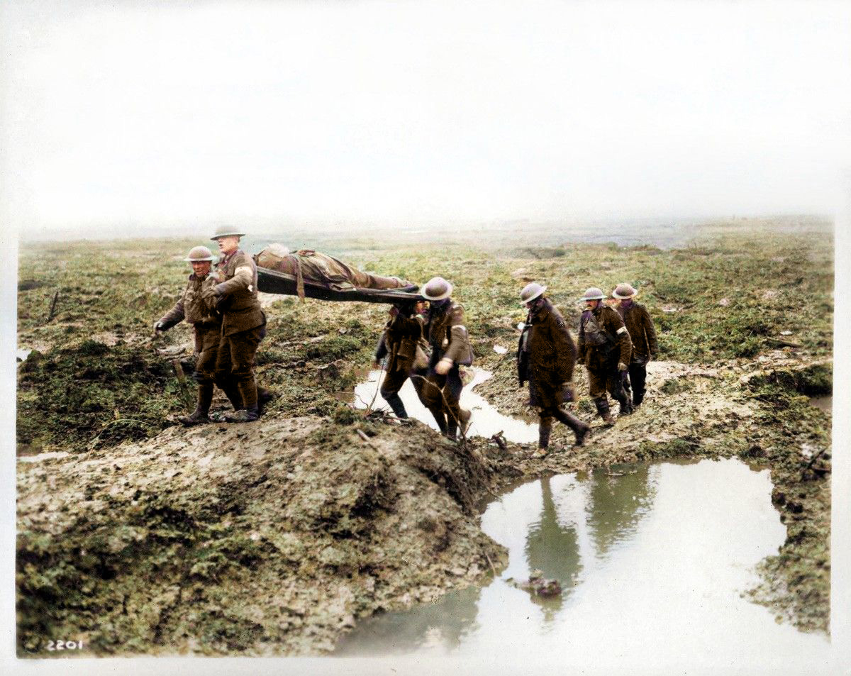 Canadian troops carry a wounded man to the aid post