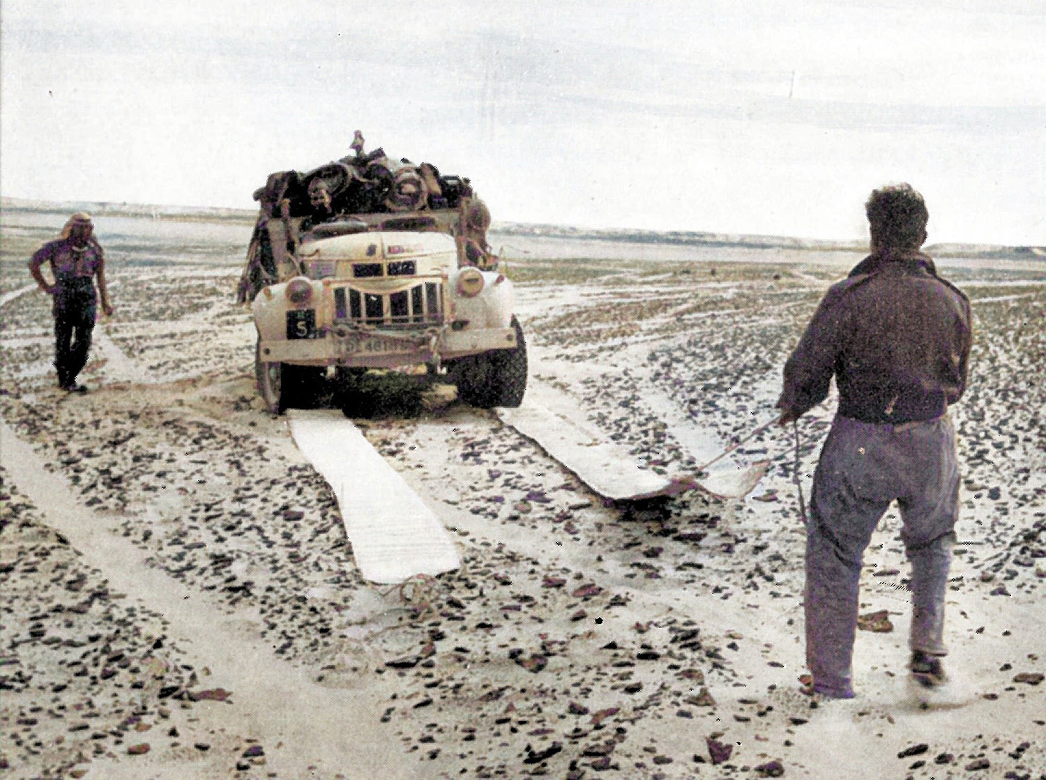 Heavily laden trucks could easily bog down in the desert. Here patrolmen use sand mats to increase the traction and drive a lorry free of the dunes