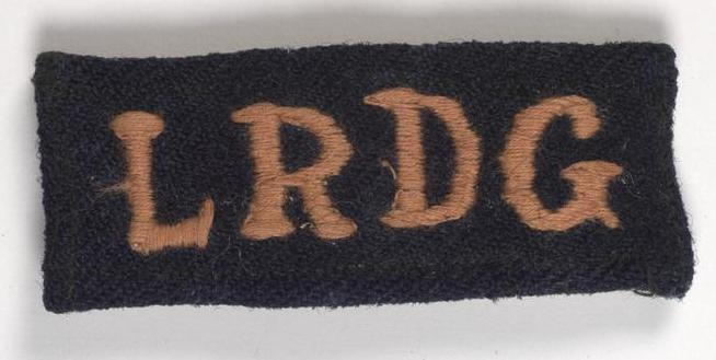 Embroidered shoulder slides were originally produced in red on a black background. Many are now pink or white due to the effects of the sun