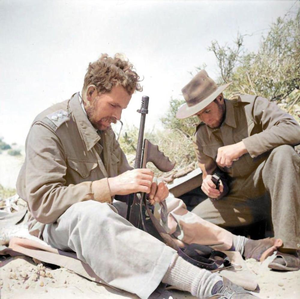 Two patrolmen clean their weapons in the desert in 1942