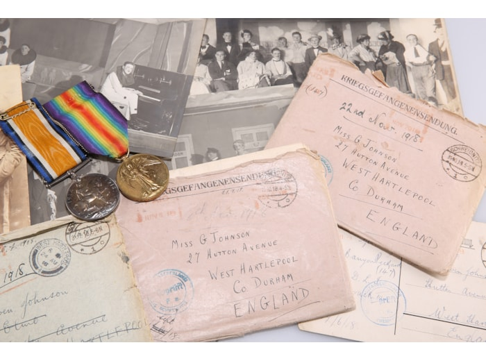 The envelopes addressed to Gwen Johnson, together with photographs and WWI medals.