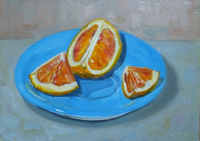 Orange segments on blue saucer