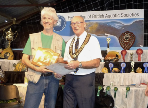 Alan Finnegan receives his Championship Shield from the FBAS Chairman Keith Cocker.