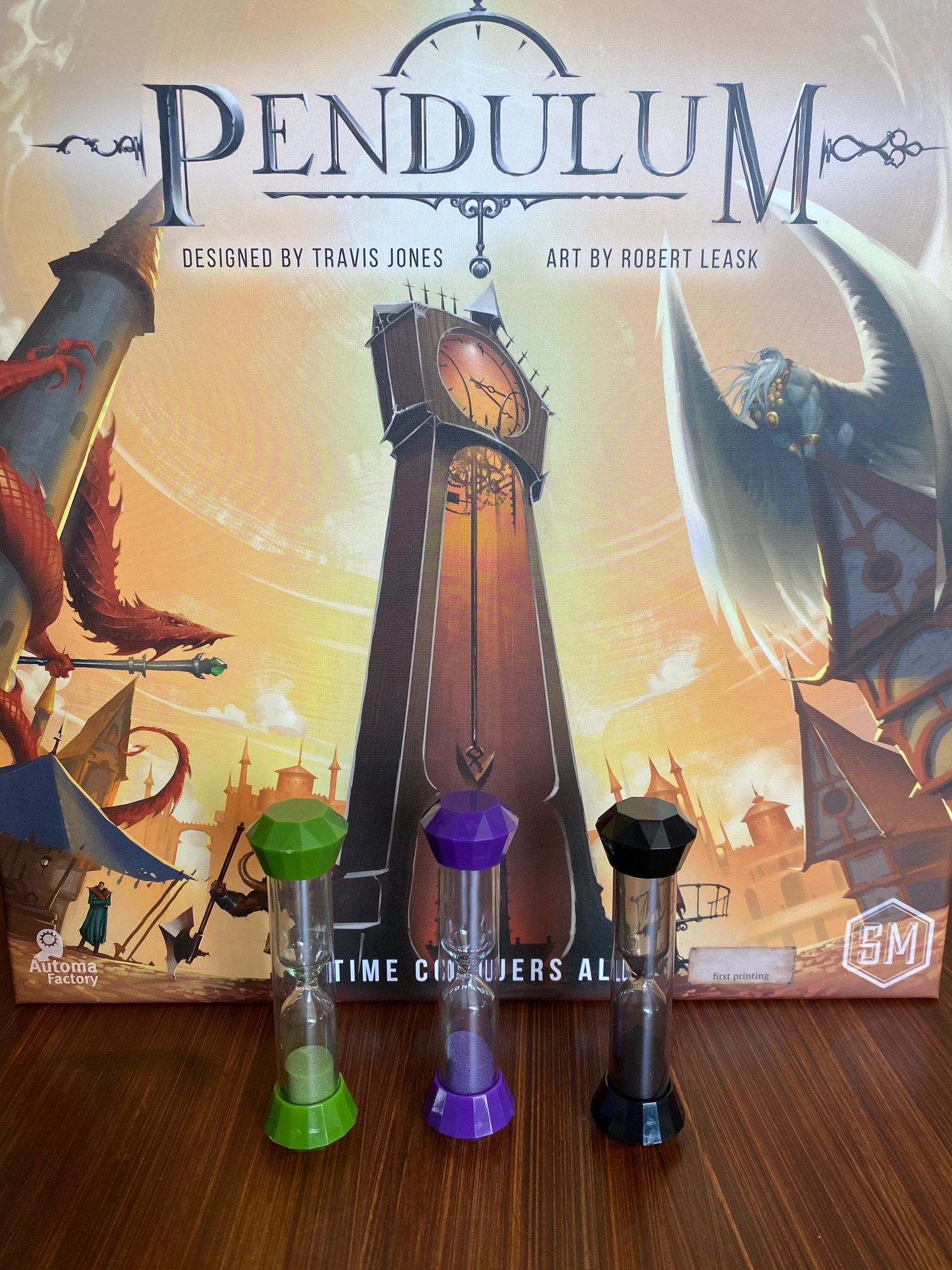 An image of the Pendulum Game Box by Stonemaier, which has a large clock tower in the center, and inf front of the box are three sand timers in green, purple, and black