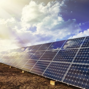 Row of photovoltaic solar panels and cloudy sky background